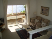 Lounge with 32 inch flat screen TV and DSTV opening via sliding door to covered terrace and sea views