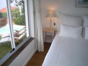 Main bedroom with window overlooking pool terrace and the sea