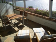 Comfortable loungers and furniture on the terrace directly overlooking the bay